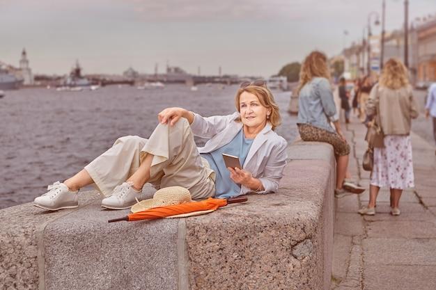 약 62 세의 나이 든 활동적인 매력적인 백인 여성이 상트 페테르부르크에서 휴대 전화를 손에 들고 캐주얼하고 우아한 천으로 강 근처에서 휴식을 취했습니다.