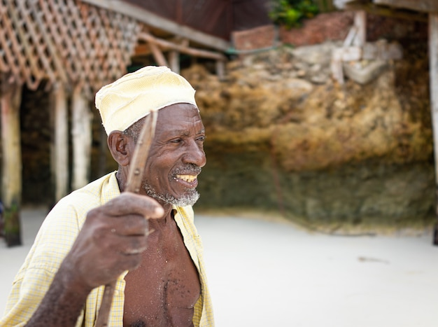 Возрасте африканская овчарка гуляет по пляжу с палкой