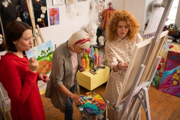 В возрасте и молодом. вид сверху на пожилую красивую женщину и молодых женщин, раскрашивающих картинку вместе