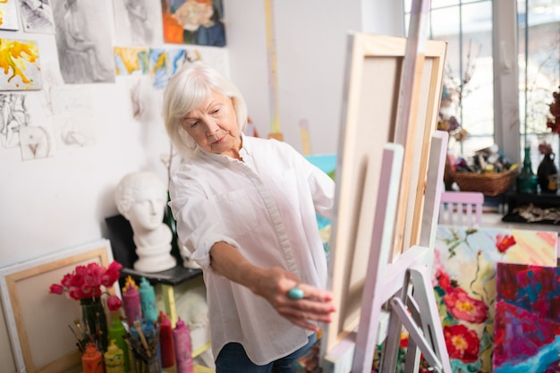 老人アーティスト。イーゼルを描く近くに立っている白いブラウスを着て短いブロンドの髪を持つ高齢の芸術家