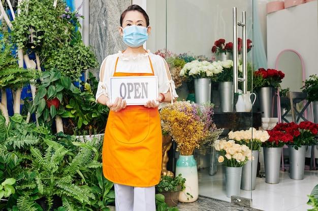 オレンジ色のエプロンでオープンサインを保持し、内部の顧客を招待する高齢のアジアのフラワーショップのオーナー