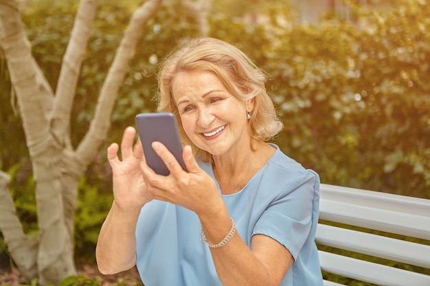 Aged attractive caucasian lady about 60 years old is using her smartphone and smiling while sitting on the bench in public park.