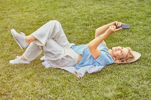 Aged attractive white woman about 62 years old in casual elegant cloth is lying down grass in public park in daytime with cell phone.