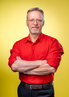 Aged bearded fit man is standing with crossed hands isolated against yellow background. red shirt. man in glasses