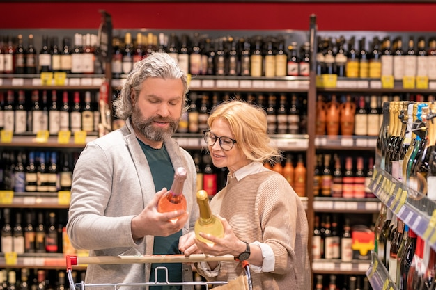 Aged bearded man with bottle of rose wine and his blond wife reading information on label while choosing alcoholic drinks