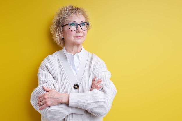 Возрасте красивая седая женщина с серьезным лицом, думающая о вопросе, очень запутанная идея, в очках, изолированные o