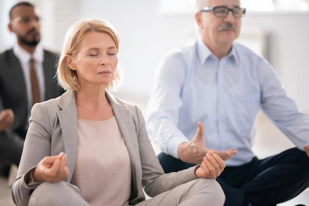 Aged blonde female in suit and her colleagues meditating at break while sitting in pose of lotus