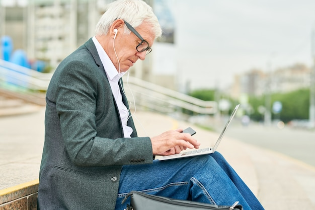 Aged businessman using laptop on stairs