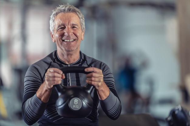 フィットネスセンターでエクササイズをしている、年をとったがフィットする男性のリフティングダンベル。