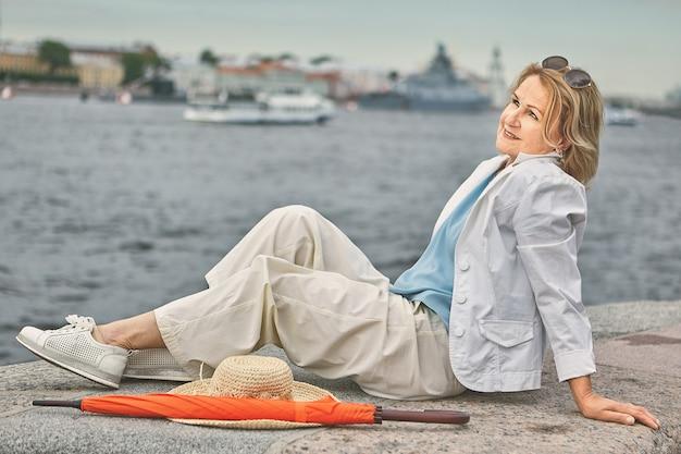 약 60 세의 백인 매력적인 웃는 여자가 시내 지역을 걷는 동안 강가에 앉아 있습니다.