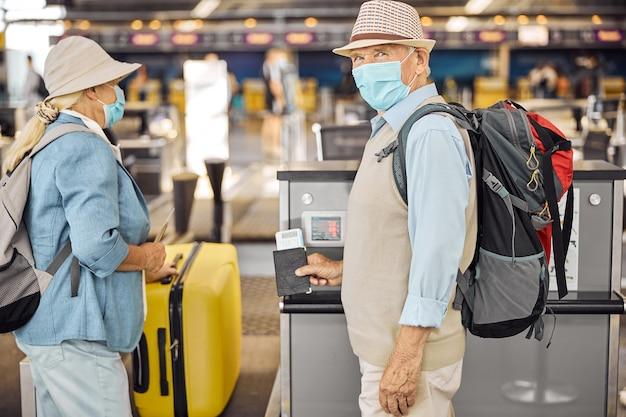 妻が荷物を降ろすのを待っているフェイスマスクの白人男性