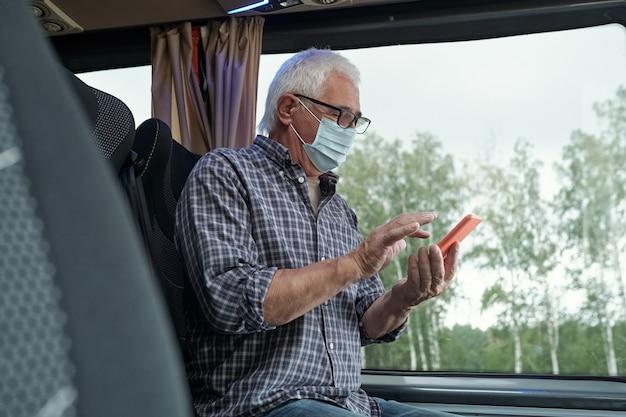 Пожилой кавказский мужчина в маске и очках сидит у окна и пользуется телефоном, отправляя смс в автобусе