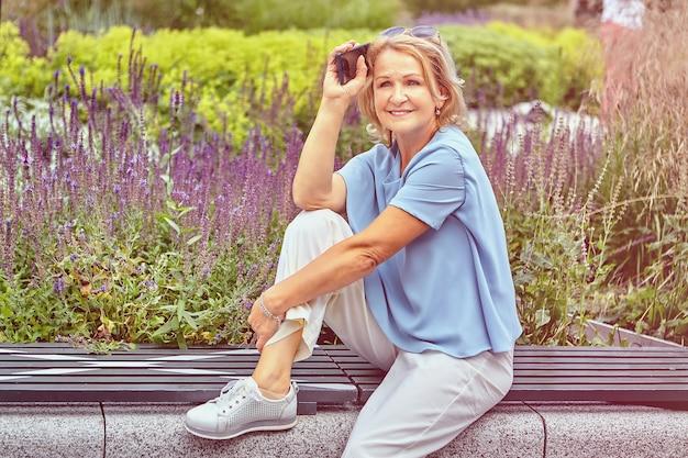 62 세 정도의 나이 든 백인 예쁜 여인이 공원 벤치에 앉아 휴대폰으로 쉬고있다.