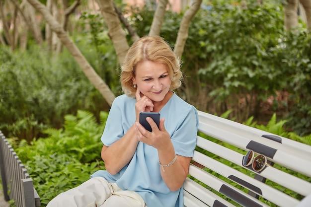 약 60 세의 백인 여성이 야외 벤치에 앉아 스마트 폰을 바라보고 있습니다.