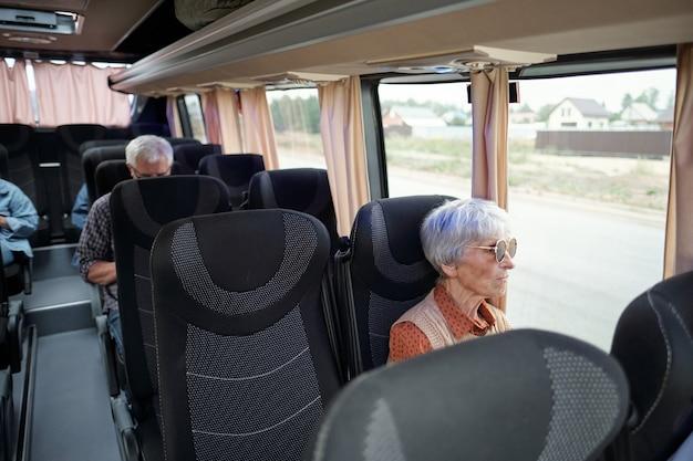 Пожилая кавказская женщина с седыми волосами сидит у окна внутри автобуса