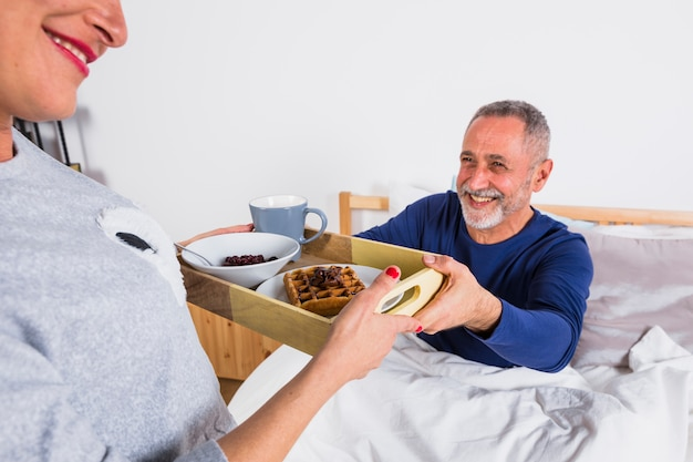 Aged cheerful woman giving breakfast to smiling man in duvet on bed