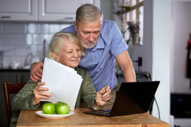 Aged couple checking finances at home using laptop, discussing planning budget together, using online banking services and calculator, holding documents in the kitchen