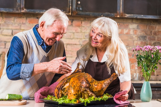 Aged couple cooking turkey in kitchen