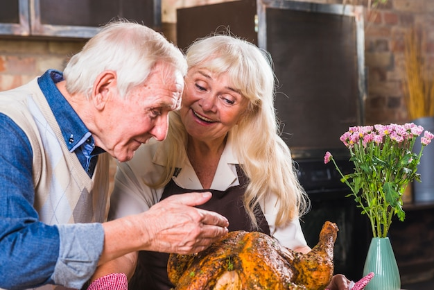 Aged couple cooking turkey