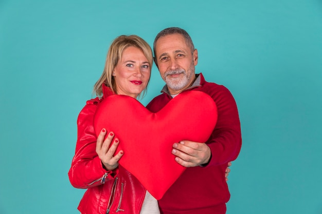 Aged couple holding toy symbol of heart