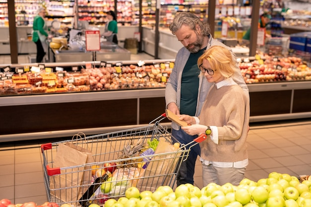Aged couple reading shopping list in notepad while moving along fruit display and pushing cart in front of themselves in supermarket