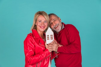 Aged couple showing toy house