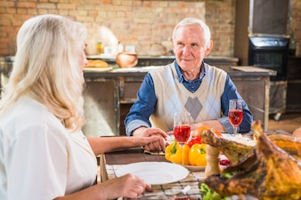 Aged couple sitting at table with food