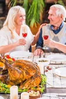 Aged couple sitting at table with roasted chicken