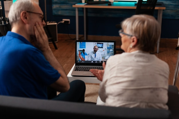 Aged couple talking on video call with dentist using laptop
