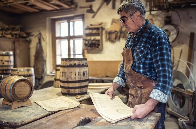 나이 든 장인은 그의 소박한 나무 통 생산 작업장에서 그림을 읽습니다.