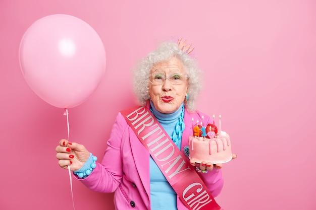 高齢の巻き毛のシニアのしわのある女性は唇を丸く保ち、キャンドルを燃やしておいしいケーキを保持し、風船を膨らませて91歳の誕生日を祝う