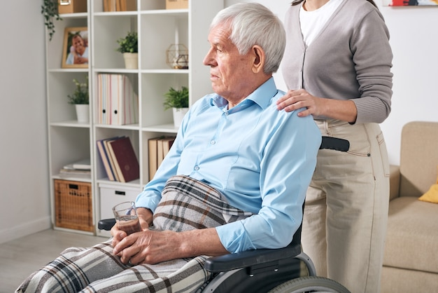 Aged disable man with glass of water sitting on wheelchair with young female caregiver standing behind and comforting him