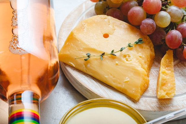 Aged dutch gouda cheese on cheeseboard with cumin herbs on table cheddar cheese with grapes wine