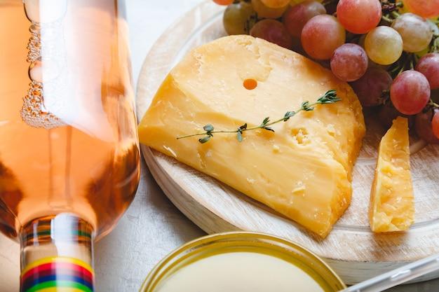 테이블에 커민 허브와 치즈 보드에 세 네덜란드 고다 치즈 포도 와인과 체다 치즈