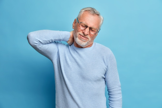 Aged exhausted bearded european man touches neck suffers from pain in neck tilts head grimaces from painful feelings needs massage dressed in long sleeved jumper isolated over blue wall
