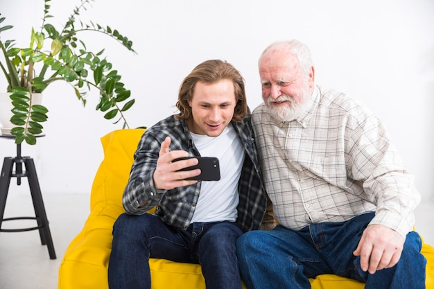 Aged father browsing smartphone with young son