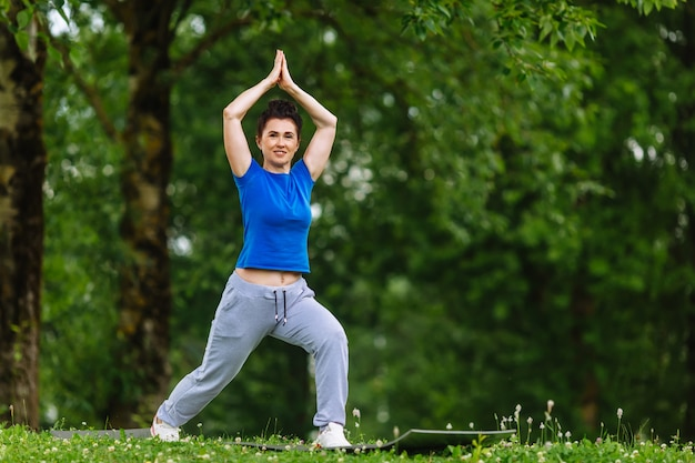 Aged female doing yoga exercise in park. senior woman practicing yoga outdor