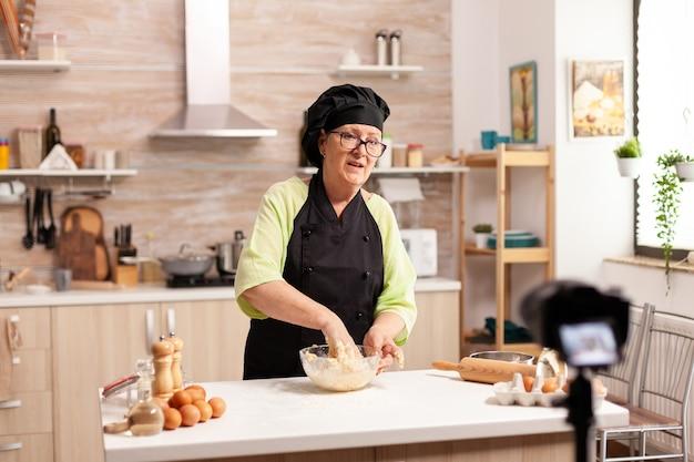 Пожилая женщина-влогер снимает в социальных сетях видео о кулинарии для интернет-канала. блогер-шеф-повар на пенсии, используя интернет-технологии, общается и ведет блог в социальных сетях с ди