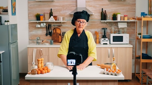 Aged female vlogger making social media video about cooking for the internet channel. retired blogger chef influencer using technology communicating, shooting blogging with digital equipment