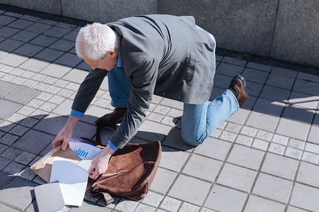 Aged good-looking educated man searching for documents putting his bad down while going to walk