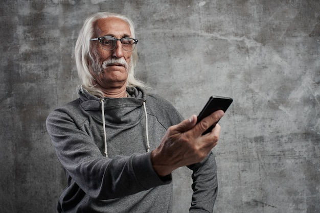 Aged gray-haired caucasian retired man looks surprised at mobile phone screen. grandfather in glasses with mustache mastering modern technology.