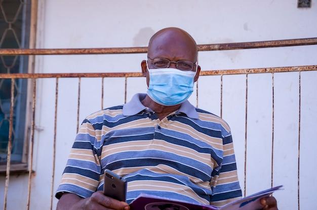 Возрасте красивый африканский мужчина в маске чувствует возбуждение, читая книгу у себя на коленях.