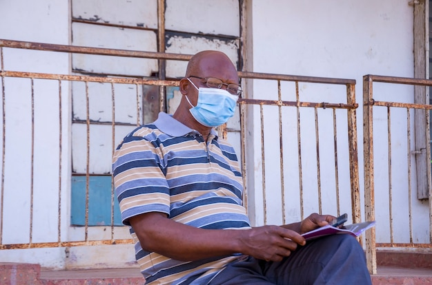 Престарелый красивый африканский мужчина в маске, предохраняющий себя от вспышки болезни в обществе и читающий книгу