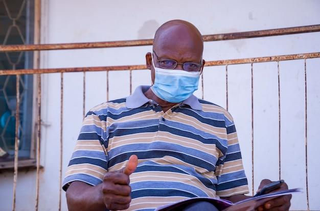 Престарелый красивый африканский мужчина в маске, предохраняющей себя от вспышки в обществе, читал книгу и поднял палец вверх.