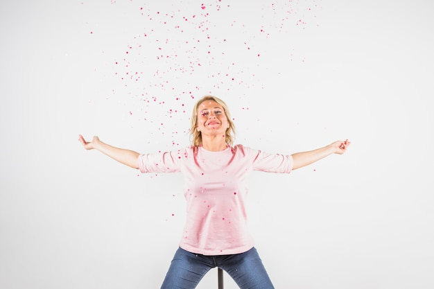 Aged happy lady in rose blouse with hands to sides between confetti