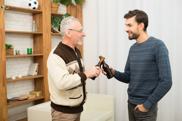 Aged happy man clanging bottles with young guy in room
