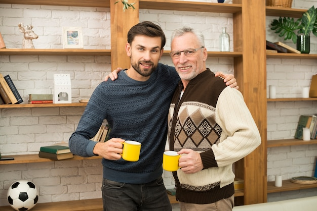 Aged happy man hugging with young guy with cups near bookshelves