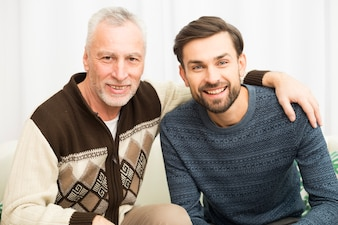 Aged happy man hugging young smiling guy on sofa