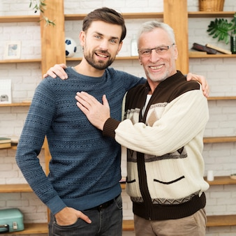 Aged happy man touching and hugging with young smiling guy