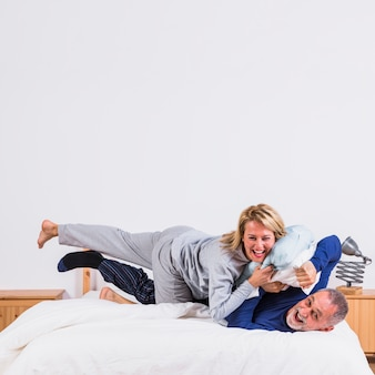 Aged happy woman lying on man with pillows on bed in bedroom